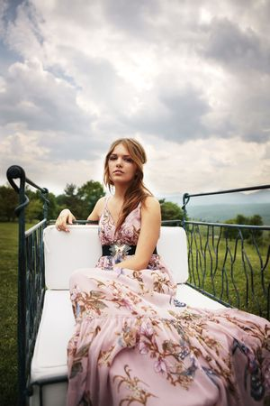 a portrait of a beautiful bridesmaid smiling in the middle of the nature seating and looking at the camera Stock Photo