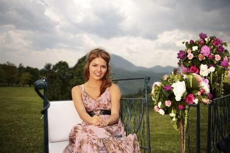 a portrait of a beautiful woman in the middle of the nature next to bouquets of colorful flowers and under a dramatic sky