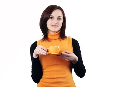 Friendly young girl with a tea cup in her hands in orange pullover vest  isolated on white background  Stock Photo