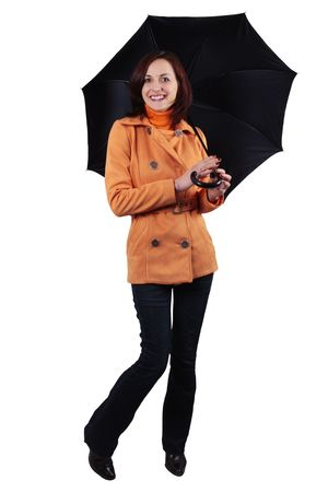 Friendly young girl under black umbrella in an orange jacket and blue jeans isolated on white background