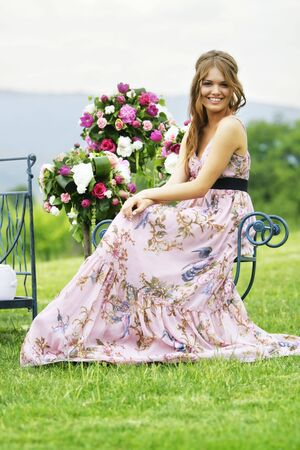 a portrait of a beautiful bridesmaid smiling in the middle of the nature seating next to bouquets of colorful flowers Stock Photo