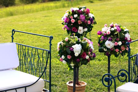 Beautiful Bouquets of peonies and flowers as wedding arrangements in the green beautiful field of grass next to artistic white seats