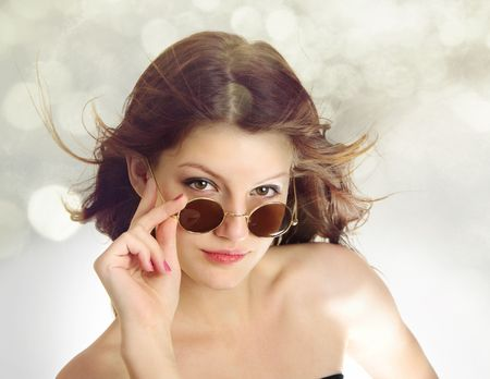 Superior funky look of teenage girl with hair in the wind and vintage glasses isolated on white background
