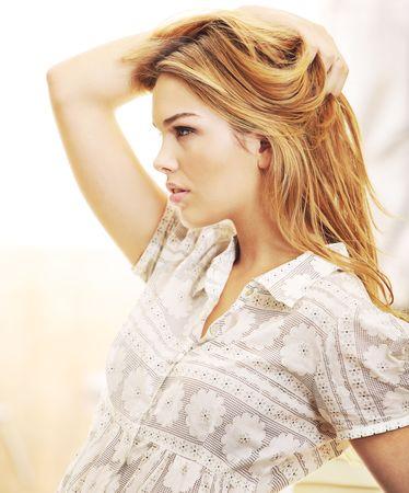 blusa: Perfil de modelo de moda bell�sima rubia jugando con el pelo y posando en una luz de color interior