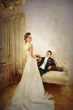 Full length of bride and groom in luxurious and with a vintage look interior with dress seen from the rear photo