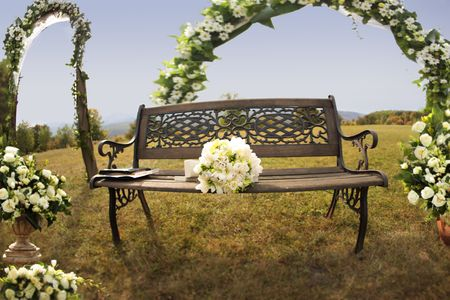Bride's bouquet on a bench in the middle of the nature near flower arch and decorations in a green beautiful field on a weeding day Stock Photo - 6355193