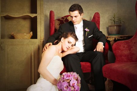 lux: Bride relaxed in Groom arms on a arm chair in beautiful vintage interior next to red sofa