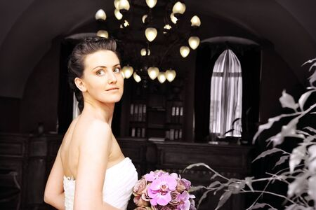 Bride with bouquet of flowers looking over her shoulder smiling in beautiful interior