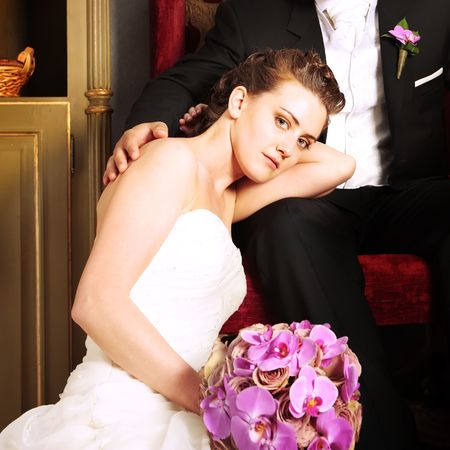 Bride relaxed in Groom arms on a arm chair in beautiful vintage interior next to red sofa