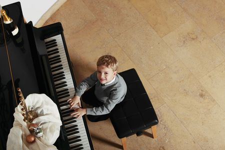 Child playing the piano smiling inside a home in the hole way elevated view looking above to the camera Stock Photo
