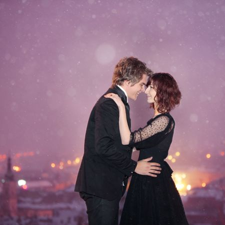 amore: Profile of Romantic Couple smiling looking into each others eyes against the city at night on valentines day