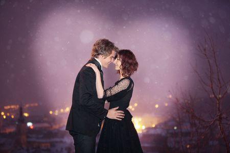 dia y noche: Perfil de la pareja de rom�ntico sonrientes mirando en cada uno de los otros ojos contra la ciudad en la noche del d�a de San Valent�n