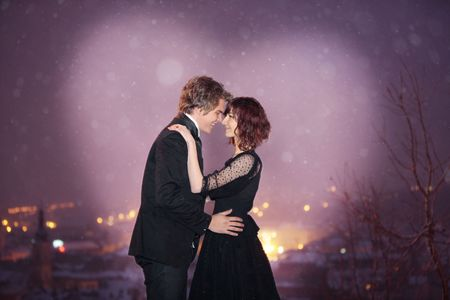 winter night: Profile of Romantic Couple smiling looking into each others eyes against the city at night on valentines day