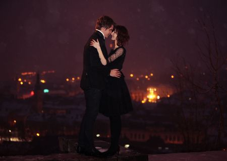 each: Full length profile of Romantic Couple looking into each others eyes against the city at night on valentines day