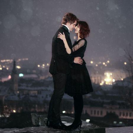 romantico: Perfil de longitud completa de la rom�ntica pareja mirando en cada uno de los otros ojos contra la ciudad en la noche del d�a de San Valent�n