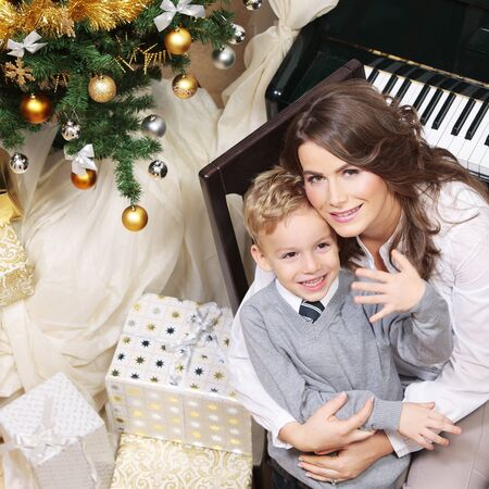 Mother hugging son on Christmas night with tree and gifts around near the piano smiling and laughing