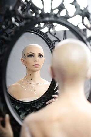 Real bald cancer survivor woman looking calmly into the mirror photo