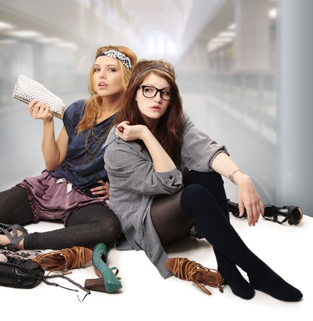 Cool teenage girls fashionista with headpiece standing on the floor surrounded by accessories, shoes and blings