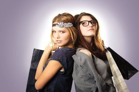 Attractive and cool looking teenage girls with headpieces holding shopping bags on gradient background photo