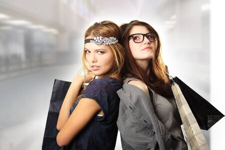 Attractive cool looking teenage girls holding shopping bags photo