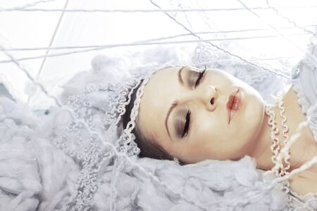 Close-up of sleeping young beauty with perfect skin artificial eyelashes eye liner and foundation in artistic setup