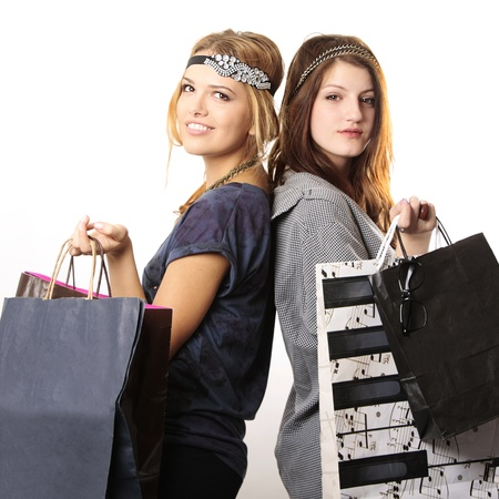 Attractive cool looking teenage girls with headpieces holding shopping bags and looking at the camera on white background Stock Photo - 8852950