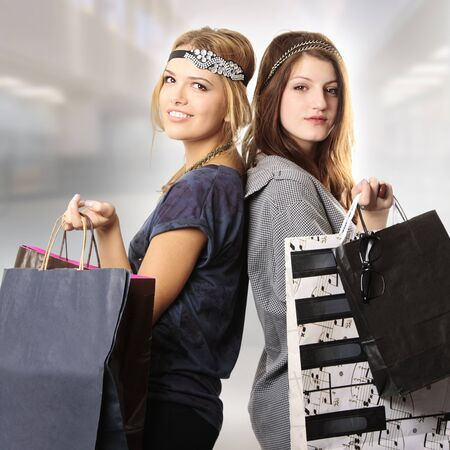 Attractive cool looking teenage girls with headpiece shopping at the mall looking at the camera holding bags  Stock Photo