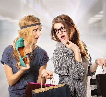 Attractive cool looking teenage girls with headpiece shopping at the mall looking at the camera holding bags  photo