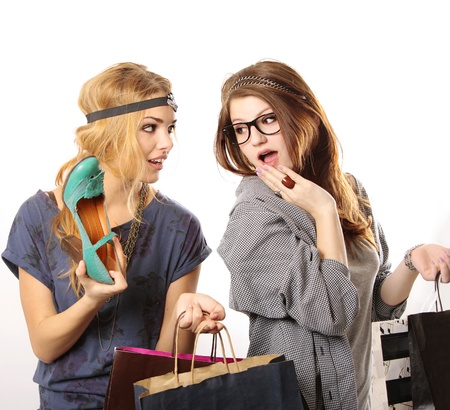 Attractive cool looking teenage girls with headpieces holding shopping bags and looking at the camera on white background