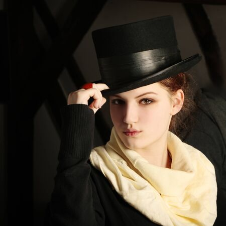 Classic young lady with black hat and beige scarf looking at the camera photo