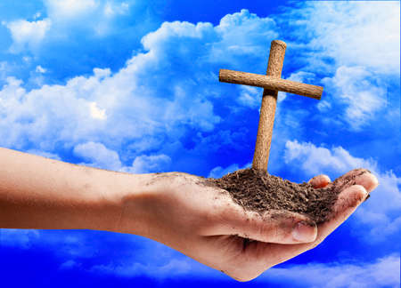 Hand offering a cross on blue sky background Banco de Imagens