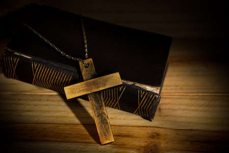 Cross in bible on wooden background