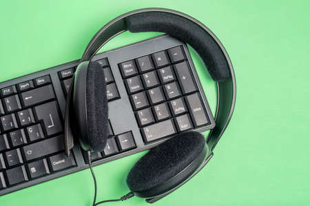 Keyboard, headphone in background green