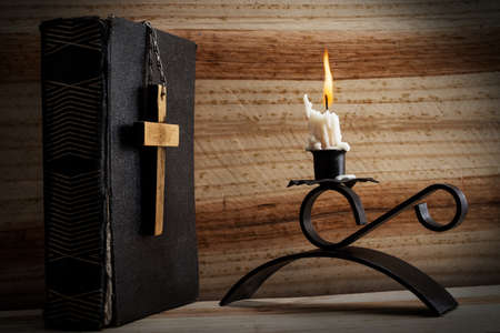 Bible, cross and candlelight