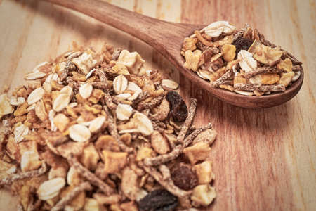 Cereals on wooden table with wooden spoon