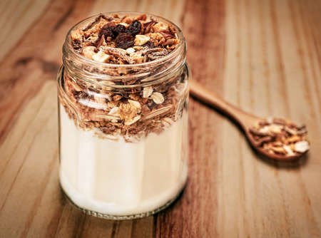 Cereals on wooden table with wooden spoon in glass