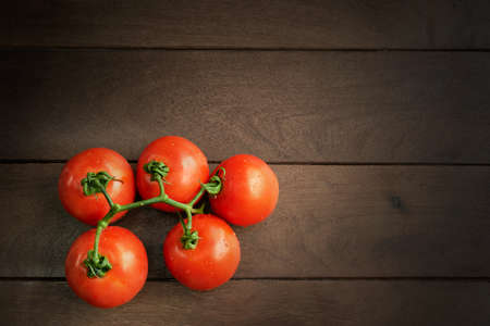 tomatoes on rustic wooden table, strut light on object, overhead