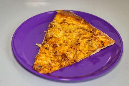 A slice of pizza on a purple plastic plate Фото со стока