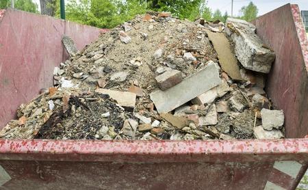 Debris in a red metal container. Broken bricks from the demolition of the building. 版權商用圖片