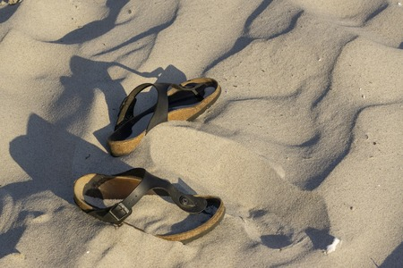 sandals lie on the sand,womens shoes on the sand in the desert abandoned Reklamní fotografie