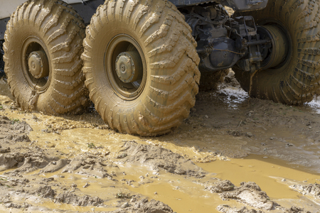 big wheels in the mud. The large wheels of a truck stuck in the mud.
