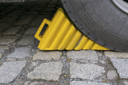 Yellow wheel chock under the big black truck wheels