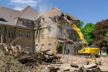 Big yellow excavator breaks down old house at summer