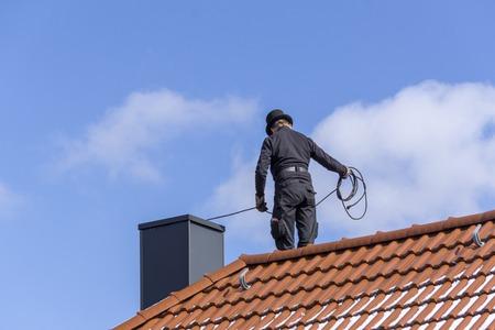 Spazzacamino che pulisce un camino in piedi sul tetto della casa, abbassando l'attrezzatura lungo la canna fumaria Archivio Fotografico