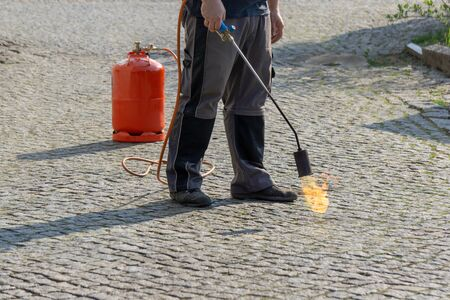Man burn weeds with torch, thermal weeds control. Environmental protection