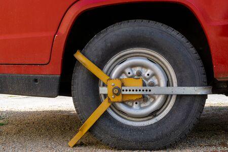 Car wheel blocked by wheel lock because illegal parking violation Stock Photo