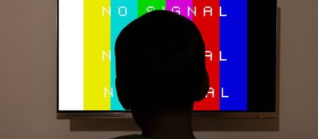 Silhouette of childs head in front of tv monitor light, End of program on TV