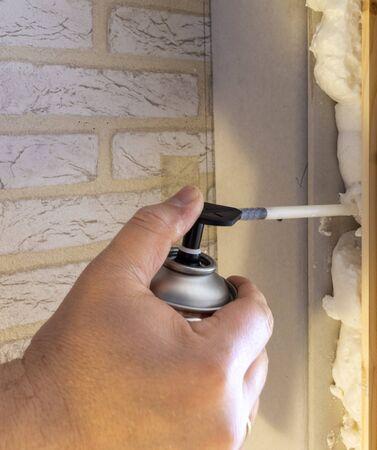 Hand holding polyurethane expanding foam glue gun applicator, a door with mounting foam Standard-Bild