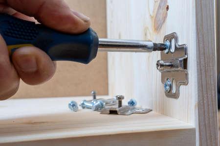 hands with screwdriver screwing hinge on a door Reklamní fotografie