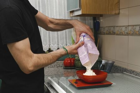 Young male cooker pouring flour in a weigh. Self making bakery dessert or breakfast Standard-Bild